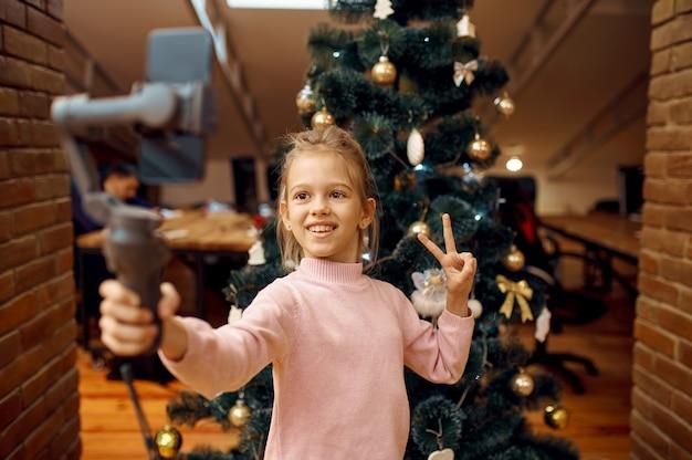 Bambina che registra blog sulla fotocamera del telefono, bambino blogger. blogging per bambini in home studio, social media per un pubblico giovane, trasmissione internet online,