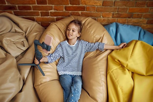 La bambina registra il blog sulla fotocamera del telefono, vista dall'alto, blogger bambino