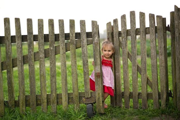 Una bambina vestita di rosso guarda fuori da dietro una staccionata in legno.