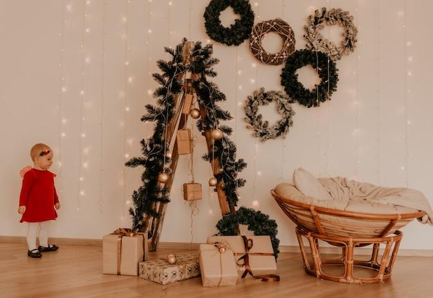 La bambina in vestito rosso corre minimalismo leggero in stile appartamento. bambino sta al muro bianco con ghirlande albero di natale con doni incartati. christmas.new year interior.valentine day celebrazione