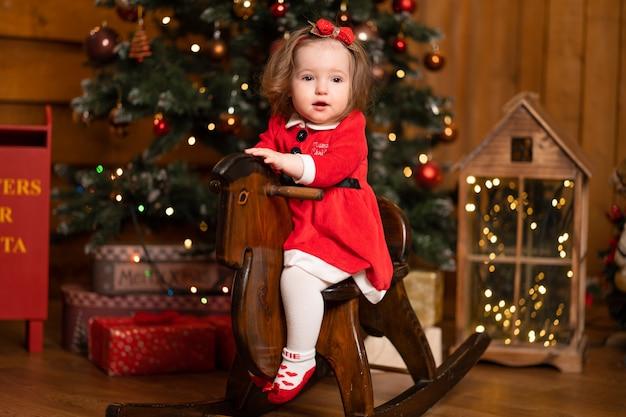 Bambina in abito rosso sul cavallo a dondolo altalena in legno. feste di natale tempo favoloso per i bambini
