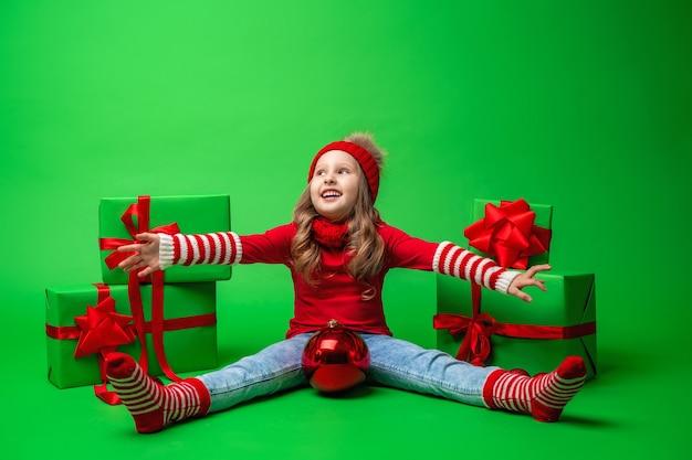 La bambina in cappello rosso si siede contenitori di regali e palla rossa di natale