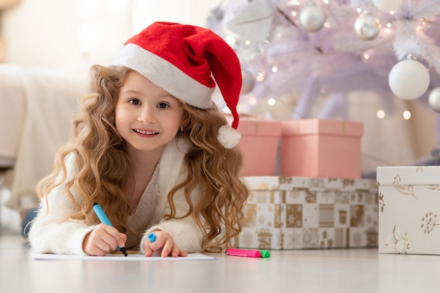 Bambina in cappello rosso che scrive una lettera a babbo natale