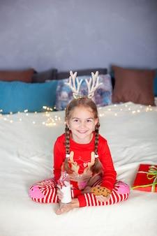 Bambina in pigiama rosso si siede con latte e biscotti alla vigilia di natale e aspetta babbo natale. il bambino mangia i biscotti con latte a casa. bambina vestita come un corno di cervo. buon natale, anno nuovo