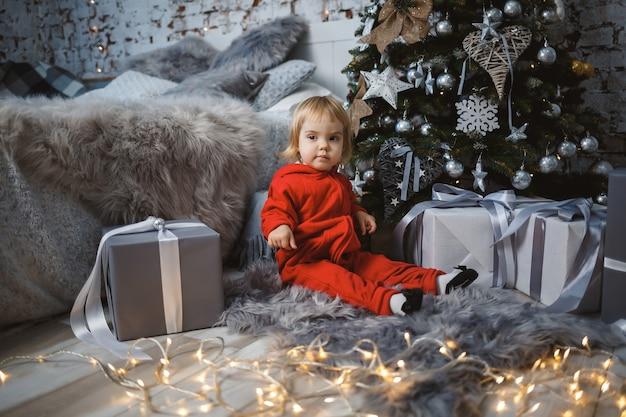 Una bambina con un maglione rosso caldo si siede sotto un albero di natale con giocattoli e regali. infanzia felice. atmosfera di festa di capodanno