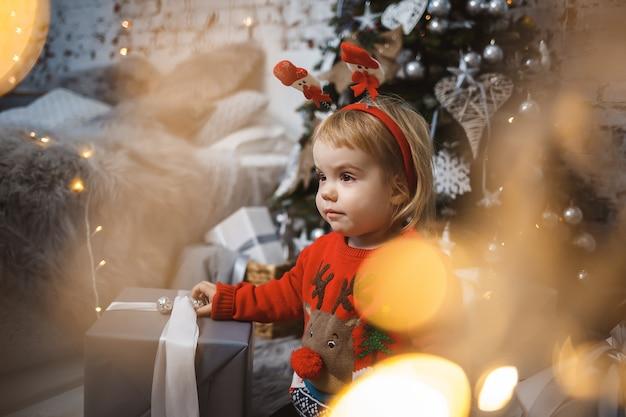Una bambina con un maglione rosso caldo siede sotto un albero di natale con giocattoli e regali con le corna in testa. infanzia felice. atmosfera di festa di capodanno