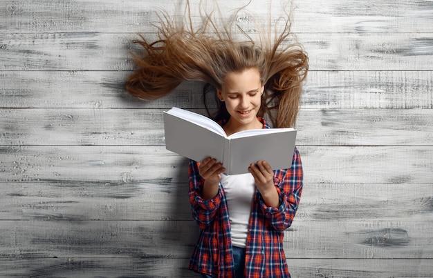 Bambina reding un libro contro il potente flusso d'aria in studio, sviluppo di capelli, effetto ventoso. bambini e vento, bambino isolato su fondo in legno, emozione bambino