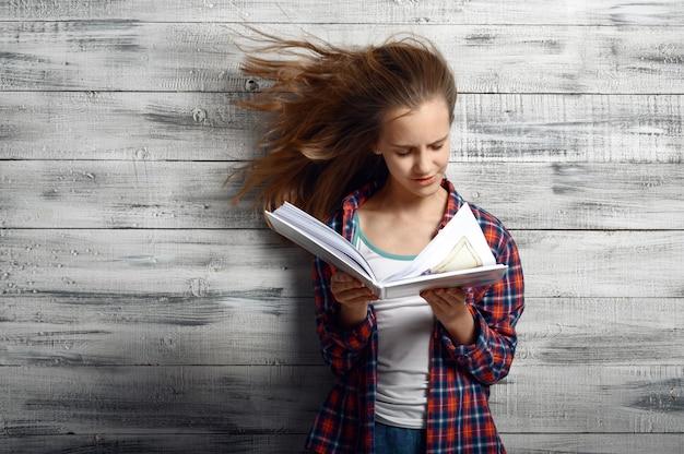 Bambina che reding un libro contro il potente flusso d'aria