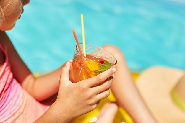 La bambina che si rilassa in piscina, che gode dell'abbronzatura, beve un succo sul materasso giallo gonfiabile in acqua in vacanza con la famiglia