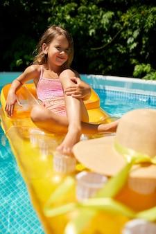 Bambina che si distende in piscina, godendo di abbronzatura sul materasso gonfiabile giallo