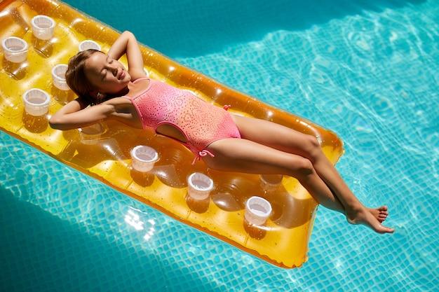 Bambina che si rilassa in piscina, si gode l'abbronzatura, nuota su un materasso giallo gonfiabile e si diverte in acqua in vacanza in famiglia, località di villeggiatura tropicale, vista dall'alto, copia spazio.