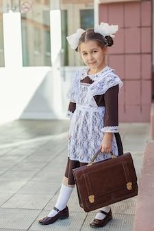 Una bambina con una divisa scolastica retrò e un grembiule bianco cammina per strada con una valigetta dopo la scuola
