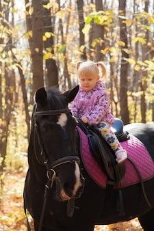 Bambina a cavallo nella foresta autunnale