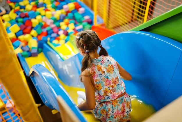 Bambina che guida su scivolo di plastica per bambini, parco giochi nel centro di intrattenimento.