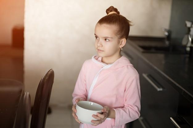 Una bambina in una veste tiene un piatto tra le mani e sta per fare colazione.