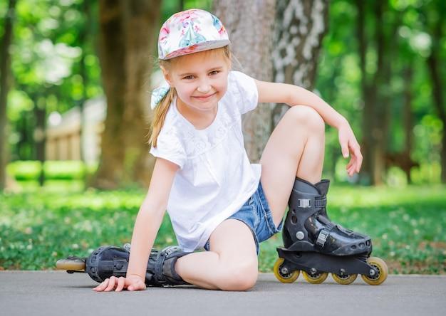 Bambina su pattini a rotelle nel parco