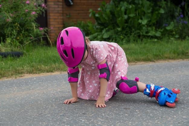 Una ragazzina pattinatrice in piena protezione è caduta sull'asfalto. il concetto di guida sicura.