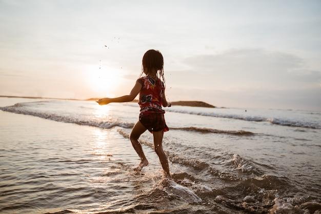 Bambina che funziona sulla spiaggia mentre gioca con acqua