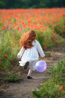 Bambina che corre in un campo di papaveri