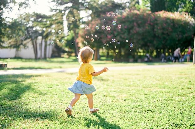 La bambina corre su un prato verde per le bolle di sapone