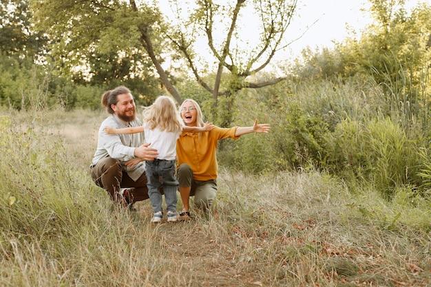 Una bambina corre tra le braccia dei suoi genitori durante una passeggiata. protezione dei bambini