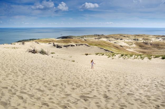Una bambina corre attraverso le dune di sabbia del mar baltico con tempo soleggiato.lituania.