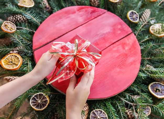 Le mani della bambina che tengono il contenitore di regalo di natale rosso su sfondo di decorazioni invernali con struttura in legno e rami spinosi verdi di abete con fette e coni di arancia secca.