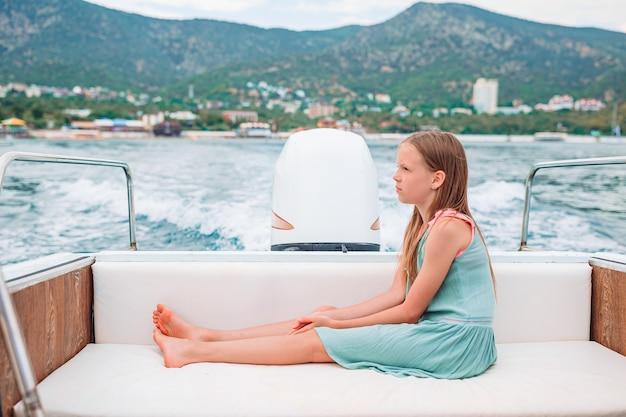 Bambina che naviga sulla barca in mare aperto e limpido