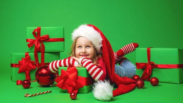 La bambina con un cappello da babbo natale è sdraiata su una confezione regalo