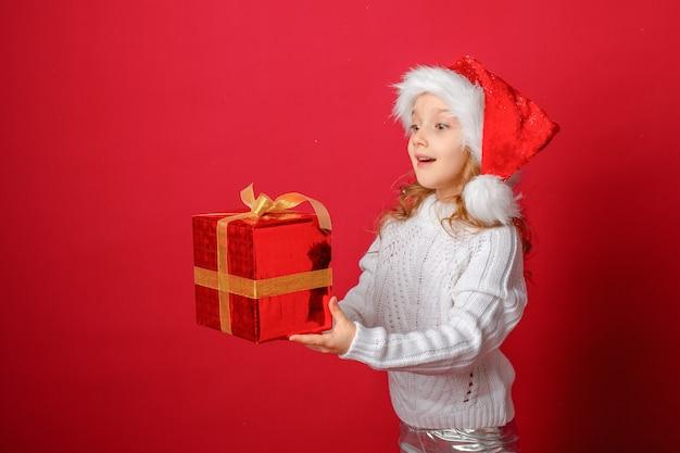 Bambina con un cappello da babbo natale su uno sfondo rosso con una torta e un regalo