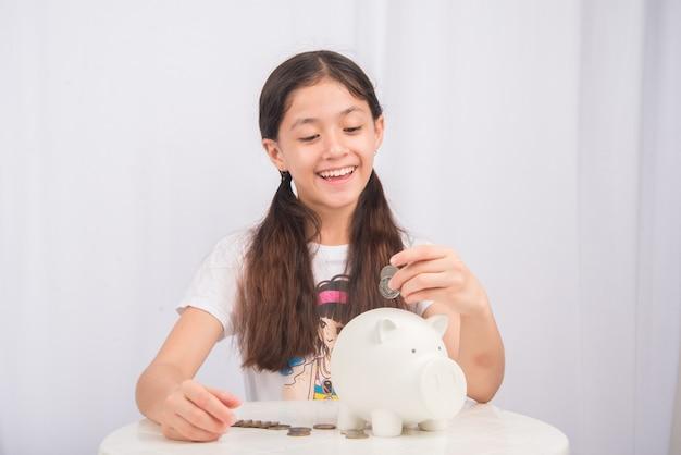 Bambina risparmio di denaro nel salvadanaio