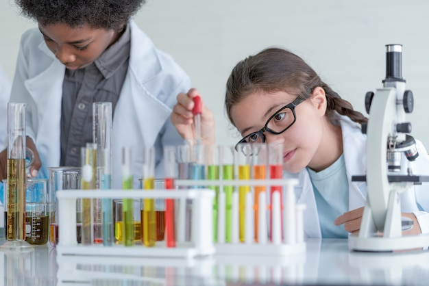 Scienziato della bambina che fa esperimenti chimici nel tubo di vetro nella stanza del laboratorio