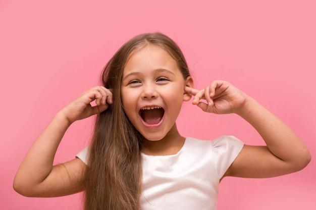 Bambina che grida tappando le orecchie con le dita