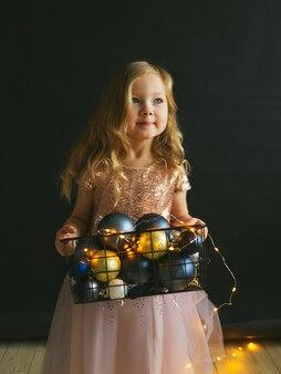 Una bambina con un vestito di paillettes sta tenendo in mano una scatola di decorazioni natalizie