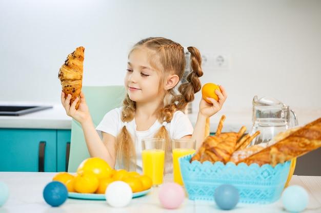 Una bambina di sette anni, con indosso una maglietta bianca, è seduta al tavolo della cucina. contiene mandarini mandarini e un croissant appena sfornato al cioccolato