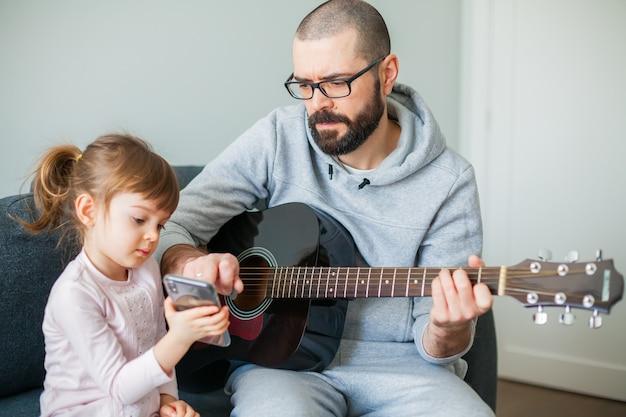 Bambina che mostra a suo padre una canzone su un telefono. l'uomo suona la chitarra per lei.