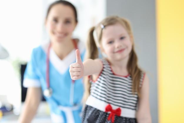 Bambina che mostra pollice in su al primo piano dell'appuntamento dal medico