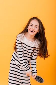 Bambina che canta usando una spazzola per capelli come microfono