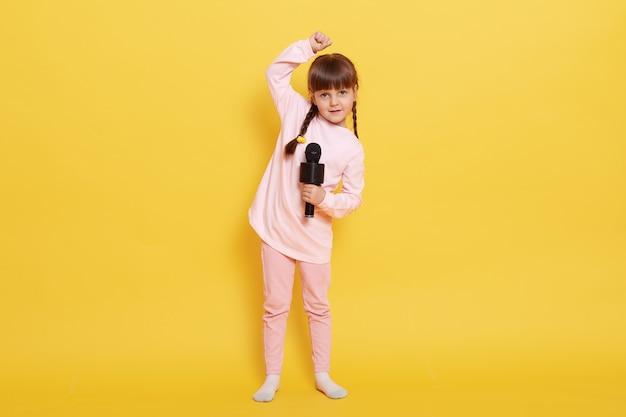 Bambina che canta con il microfono e balla, tenendo la mano alzata, guardando direttamente, indossando abiti casual rosa, bambina carina con trecce organizza un concerto contro il muro giallo.