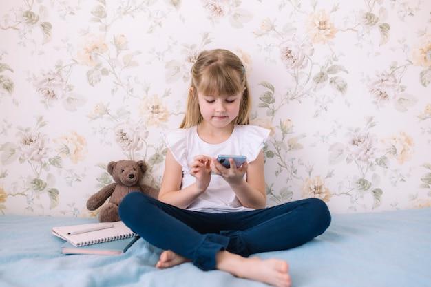 Una bambina si siede sul letto nell'elegante camera da letto, tenendo il telefono e legge qualcosa in smartphone. concetto di comunicazione