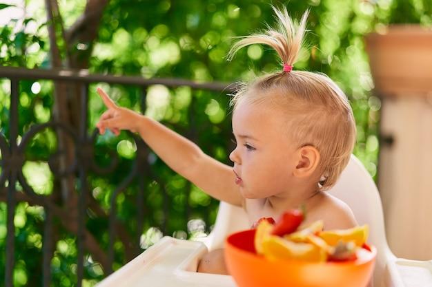 La bambina si siede su un seggiolone sul balcone e punta il dito in lontananza