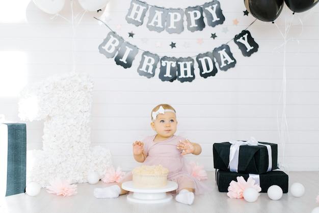 Bambina si siede vicino a una torta, festeggia il suo primo compleanno