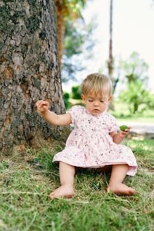La bambina si siede vicino a un platano