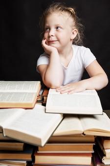 La bambina si siede su una pila di libri e sogni. istruzione e formazione.