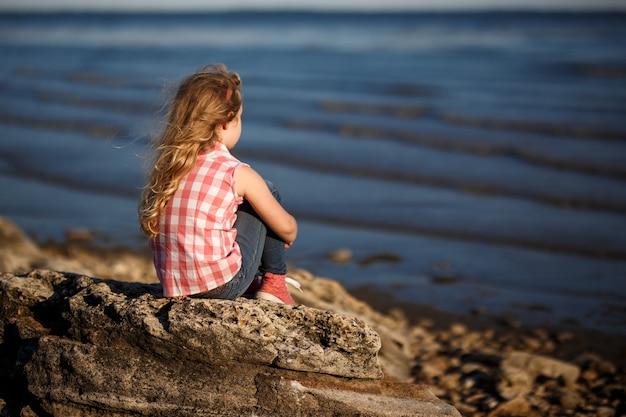 La bambina si siede su una spiaggia rocciosa e guarda il mare.