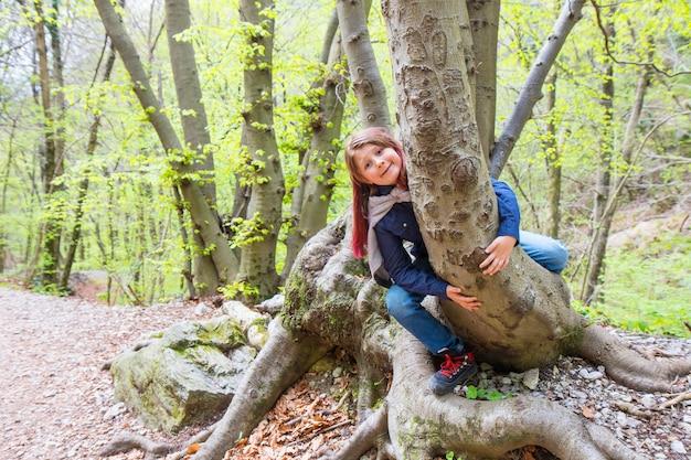 Bambina seduta a cavalcioni di un tronco in una foresta