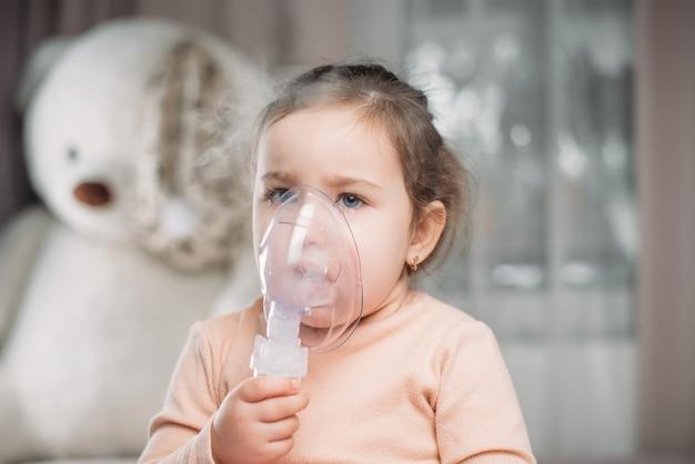 Bambina seduta sul letto in camera da letto con maschera ad ossigeno