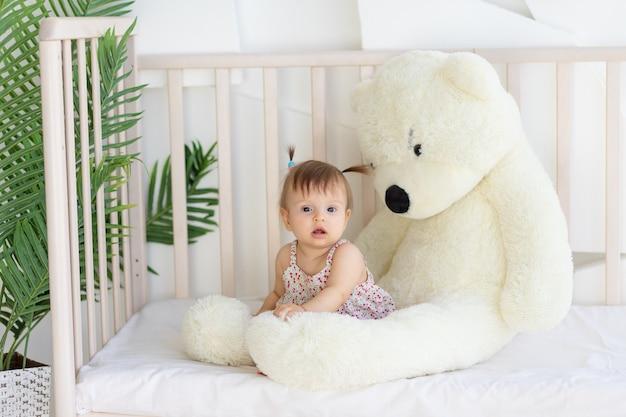 Bambina seduta in una culla a casa con un grande orsacchiotto
