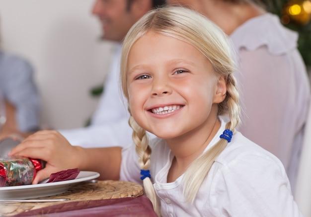 Bambina che si siede al tavolo da pranzo che sorride al natale