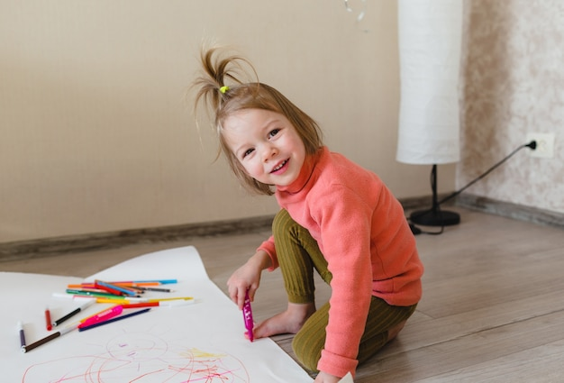 Una bambina, seduta sul pavimento, gode della creatività, disegnando con le matite e colorando le immagini negli album.